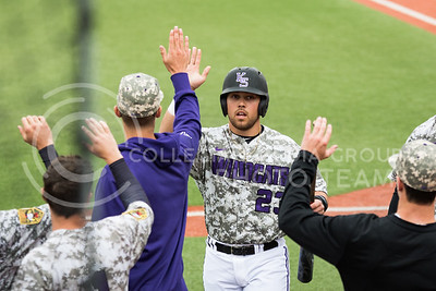 Senior 1st baseman Jake Scudder high-fives teammates after socring at the K-State baseball game against Eastern Illisnois University at Tointon Family Stadium on Mar. 5, 2017. (John Benfer | The Collegian)