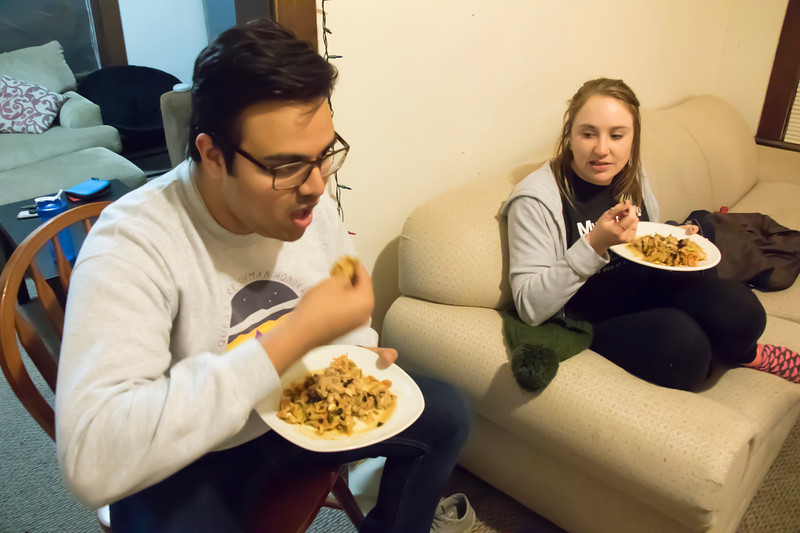 Rajat Kodira (left), freshman in industrial engineering, eats Sri Lankan food the traditional way — with his hands — at Eating Around the World on Sunday, Feb. 25, 2018, in a house on Laramie Street near the Kansas State University campus. (Tiffany Roney | Collegian Media Group)