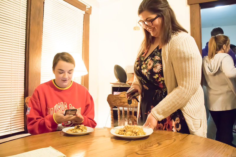 Helene Waldeck (left), junior in family studies and human services, and Haley Hannaman, graduate student in student development, prepare to eat Sri Lankan food at Eating Around the World on Sunday, Feb. 25, 2018, in a house on Laramie Street near the Kansas State University campus. The food was cooked by Meenu Mohankumar, doctoral student in statistics, and Dishan Nahitiya, applications developer for Housing and Dining Services. (Tiffany Roney | Collegian Media Group)