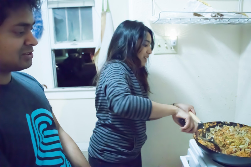 Dishan Nahitiya (left), applications developer for Housing and Dining Services, and Meenu Mohankumar, doctoral student in statistics, cook Sri Lankan food at Eating Around the World on Sunday, Feb. 25, 2018, in a house on Laramie Street near the Kansas State University campus. (Tiffany Roney | Collegian Media Group)