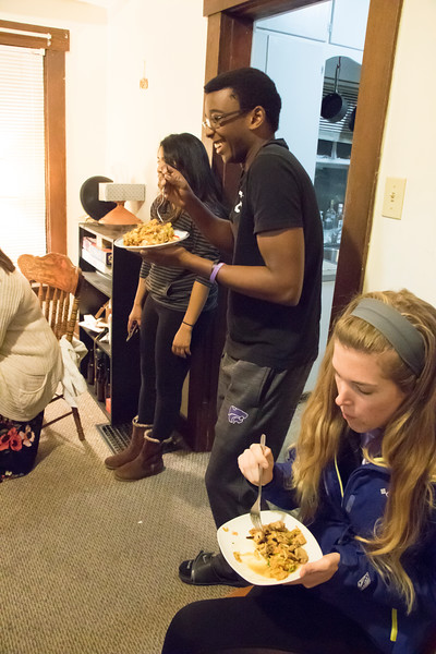 Tony Ngassi (center), junior in biology, laughs with other attendees at Eating Around the World on Sunday, Feb. 25, 2018, in Ngassi's house near the Kansas State University campus. On that Sunday, attendees ate Sri Lankan food prepared by Meenu Mohankumar (back left), doctoral student in statistics, and Dishan Nahitiya (not pictured), applications developer for Housing and Dining Services. (Tiffany Roney | Collegian Media Group)