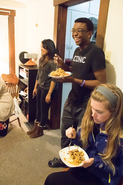 Meenu Mohankumar (far left), doctoral student in statistics, watches as attendees at Eating Around the World eat food she and Dishan Nahitiya, applications developer for Housing and Dining Services, prepared for attendees on Sunday, Feb. 25, 2018. Tony Ngassi (center), junior in biology, co-hosted the dinner, along with Ramin Rostampour (not pictured), senior in civil engineering. (Tiffany Roney | Collegian Media Group)