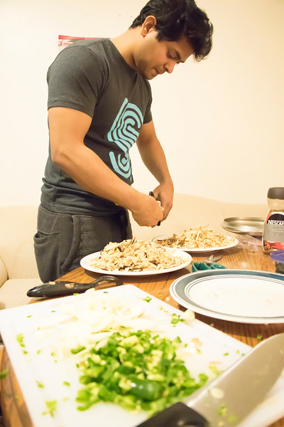 Dishan Nahitiya, applications developer for Housing and Dining Services, cuts Sri Lankan flatbread for Eating Around the World on Sunday, Feb. 25, 2018, in his house. (Tiffany Roney | Collegian Media Group)