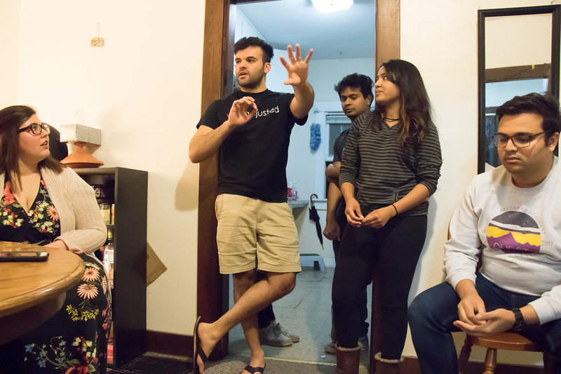 Ramin Rostampour, senior in civil engineering, tells Eating Around the World attendees how dinner will go at his house on  Sunday, Feb. 25, 2018. The Sri Lankan dinner was cooked by Dishan Nahitiya (center), applications developer for Housing and Dining Services, and Meenu Mohankumar (center-right), doctoral student in statistics. Also pictured are Haley Hannaman (far left), graduate student in student development, and Rajat Kodira, freshman in industrial engineering. (Tiffany Roney | Collegian Media Group)