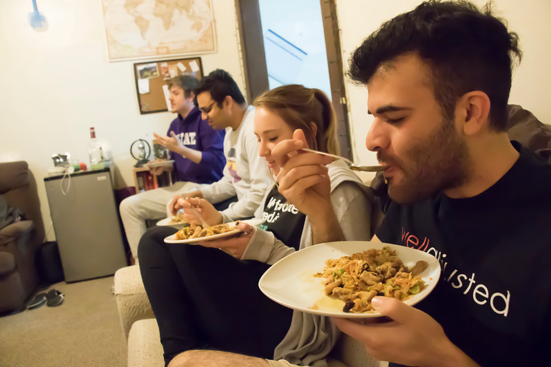 Ramin Rostampour (front), senior in civil engineering and others eat Sri Lankan food at Eating Around the World on Sunday, Feb. 25, 2018, in Rostampour's house, near the Kansas State University campus. (Tiffany Roney | Collegian Media Group)