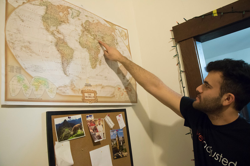 Ramin Rostampour, senior in civil engineering, points to a map where he and his housemates keep track of the countries' food they have served at Eating Around the World on Sunday, Feb. 25, 2018. (Tiffany Roney | Collegian Media Group)