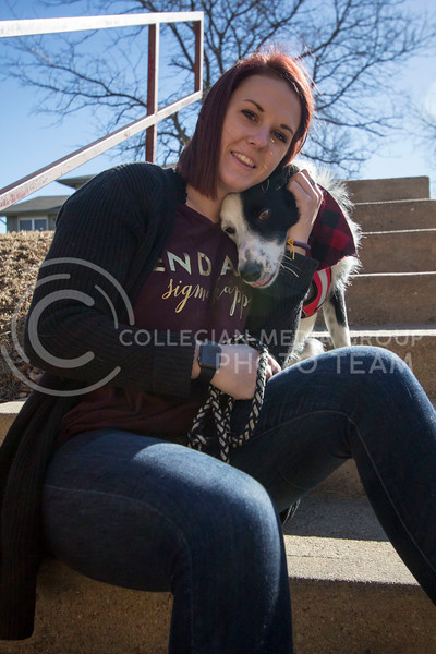 Alyssa Arnsperger, sophomore studying Animal Science Pre-Vet with a minor in Business pets her dog Milo while they are playing outside. (Sabrina Cline | Collegian Media Group)