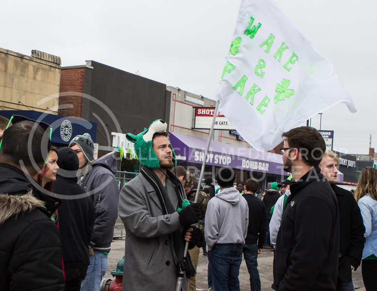 "A student waves a flag that reads ""wake and fake"" on Moro Street on the morning of Fake Patty's Day. (Regan Tokos 