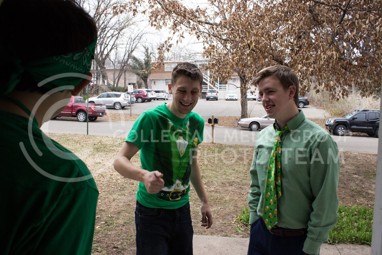 Nathan Ross, senior in fine arts, and Andrew Young, junior in regional and community planning, stand on the front porch to feel the temperature on the morning of Fake Patty's Day before beginning their mile walk to the bars in Aggieville. (Regan Tokos | The Royal Purple)