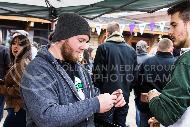 Caleb Cott, senior in sociology, checks the IDs of people participating in the festivities on Fake Patty's Day. (Regan Tokos | The Royal Purple)