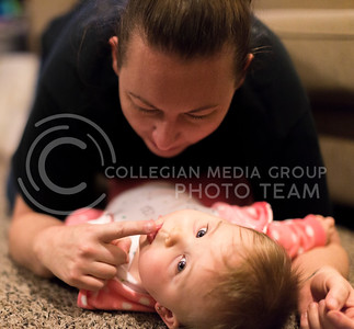 """Ashely Bowman, senior in psychology, plays on the floor with her 8-month-old daughter, Audrey Twitchel, in their apartment on Jan. 17, 2017. """"Our world litterally revolves around her,"""" Bowman said. (Emily Starkey 