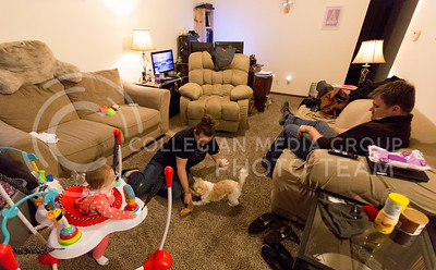 Ashely Bowman, senior in psychology, plays tug-o-war with Ammo, the family dog, as  Michael Twitchel, Masters student in architecture and their 8-month-old daughter, Audrey Twitchel look on. (Emily Starkey | The Collegian)