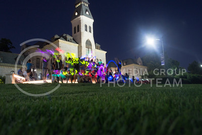 The camp members gather after the game to have a group photo taken infront of Anderson. For the special blurred affect they waved their glow sticks. (Sarah Falcon | The Collegian)