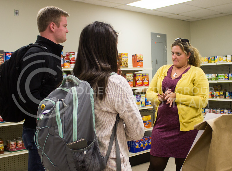 Erin Bishop, coordinator of the new campus food pantry, Cats Cupboard, talks to Olivia Baalman, senior in computer science, and Johnathan Peuchen, senior in mechanical engineering, about how Cat's Cupboard is set up at the grand opening of the pantry on Oct. 16. (Regan Tokos | Collegian Media Group)