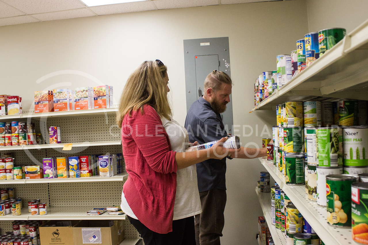 Erin Bishop, coordinator of the new campus food pantry, Cats Cupboard, stacks cans with Mark Wollard, graduate research assistant and student in family studies and human services, on Sept. 21. (Regan Tokos | Collegian Media Group)