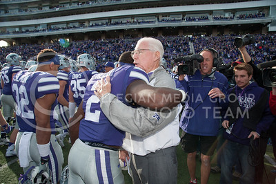 Head coach Bill Snyder hugs players after defeating KU in the Sunflower Showdown on Nov. 26, 2016, in Bill Snyder Family Stadium. The Cats won 34-19. (Evert Nelson | The Collegian)