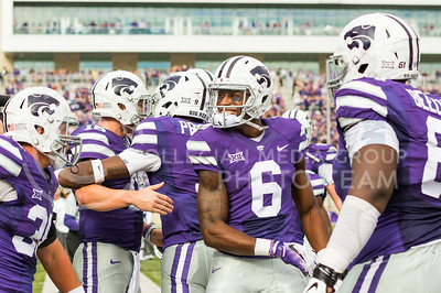 Senior wide receiver Deante Burton smiles among teammates during the K-State football game against Oklahoma State in Bill Snyder Family Stadium on Nov. 5, 2016. (John Benfer | The Collegian)