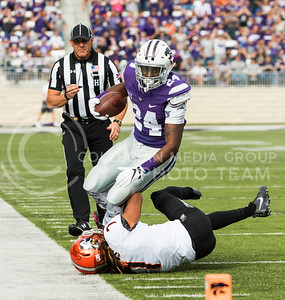 Senior running back Charles Jones runs downfield as Oklahoma State cornerback Ramon Richards starts to tackle Jones during the K-State football game against OSU in Bill Snyder Family Stadium on Nov. 5, 2016. (John Benfer | The Collegian)