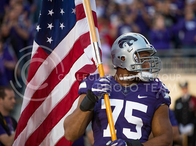 Senior defensive end Jordan Willis carries the American flag out of the tunnel at the start of the football game between K-State and Texas Tech on Oct. 8, 2016, in Bill Snyder Family Stadium. (Emily Starkey | The Collegian)