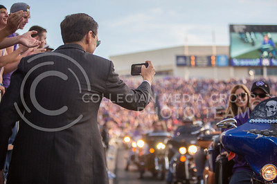 Athletic director John Curie takes a photo of motorists riding in the stadium as part of Harley Day before the start of the K-State and Texas Tech football game on Oct. 8, 2016, in Bill Snyder Family Stadium. (Emily Starkey | The Collegian)