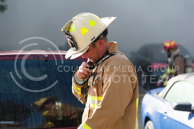 A chief for Manhattan Fire Department speaks into his radio during the fire at Founders Hill on Oct.17, 2016. (Evert Nelson | The Collegian)