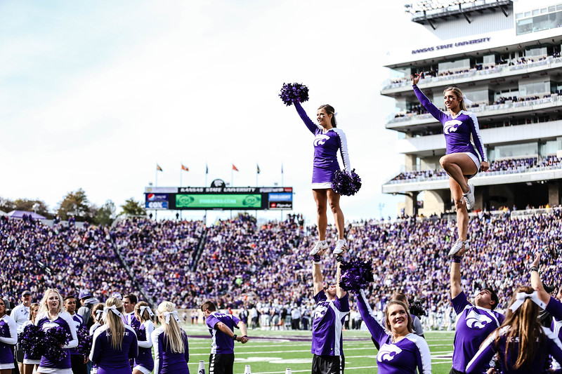The cheer team waves to the crowd during the K-State football game against Oklahoma State in Bill Snyder Family Stadium on Oct. 13, 2018. The Wildcats defeated the Cowboys 31-12. (Emily Lenk | Collegian Media Group)