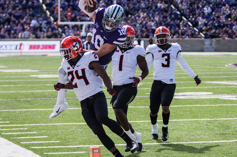 Sophomore Quarterback Skyler Thompson runs the ball, leaping over defenders towards the end zone in K-State's football game against Oklahoma State in Bill Snyder Family Stadium on Oct. 13, 2018. The Wildcats defeated the Cowboys 31-12. (Logan Wassall | Collegian Media Group)