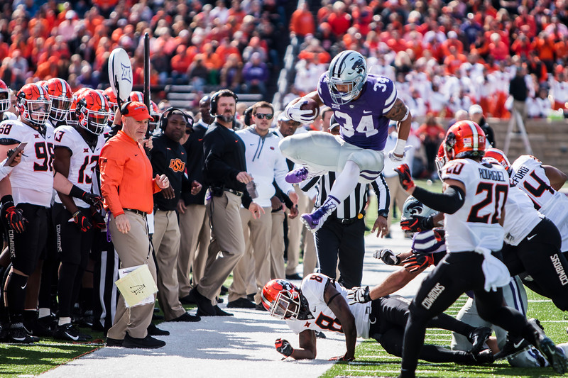 Junior running back Alex Barnes leaps over defenders while running the ball in K-State's football game against Oklahoma State in Bill Snyder Family Stadium on Oct. 13, 2018. The Wildcats defeated the Cowboys 31-12. (Logan Wassall | Collegian Media Group)