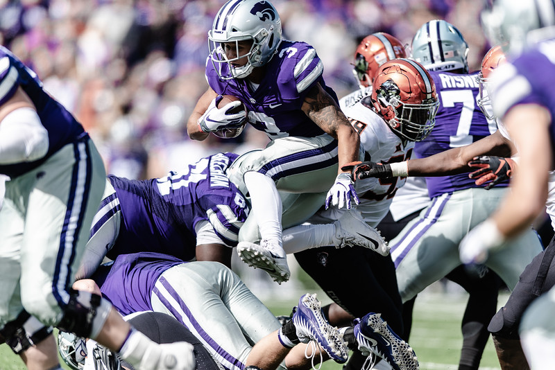 Kansas State senior running back Dalvin Warmack jumps over the Cowboy line of defense as he runs down the field in hopes of a Wildcat touchdown. On Saturday, the Kansas State Wildcats faced off against the Oklahoma State Cowboys and won with a final score of 31-12 at Bill Snyder Family Stadium. (Olivia Bergmeier | Collegian Media Group)