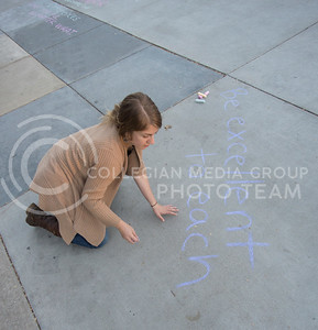 Christine Carson, graduate student in biology, chalks reassuring messages on Bosco Plaza following the results of the 2016 election on Nov. 9, 2016. (George Walker | The Collegian)