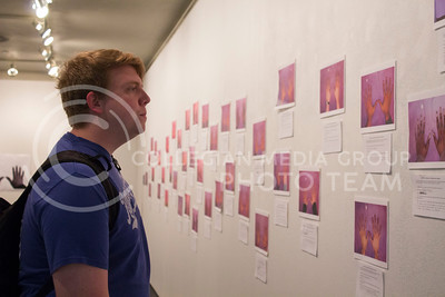 Jordan Martin, junior in computer science and mathematics, looks at photos in the art gallery in the Student Union on April 13, 2017. (Maddie Domnick | The Collegian)