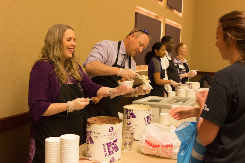 Sara Thruston, Director of International Students and Scholar Services, and Jay Stephens, Vice President for Human Capital Services, serve Call Hall ice cream to students at the Grad bash on May 3 at the Alumni Center. (Alex Masson | Collegian Media Group)