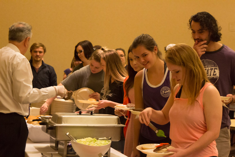 Students at the Grad Bash go through the buffet line with food served by Pat Bosco, Dean of Students and Vice President of Student Life on May 3 at the Alumni Center. (Alex Masson | Collegian Media Group)