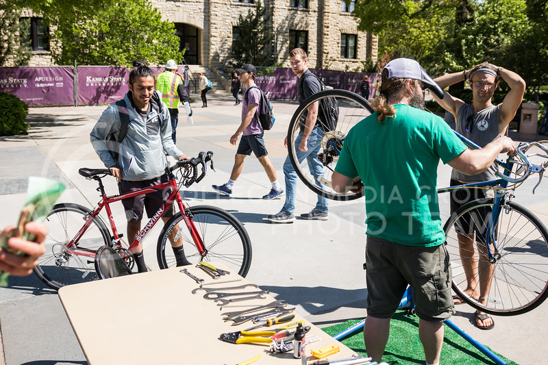 Brew Bros' Clint McAllister tunes up a bicycle at the Green Apple Bikes Ride2Campus event in Bosco Plaza on Apr. 24, 2017. (John Benfer | The Collegian)