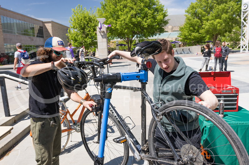 Pathfinder's Hayden Wylie and Miranda Martin tune up a bicycle at the Green Apple Bikes Ride2Campus event in Bosco Plaza on Apr. 24, 2017. (John Benfer | The Collegian)