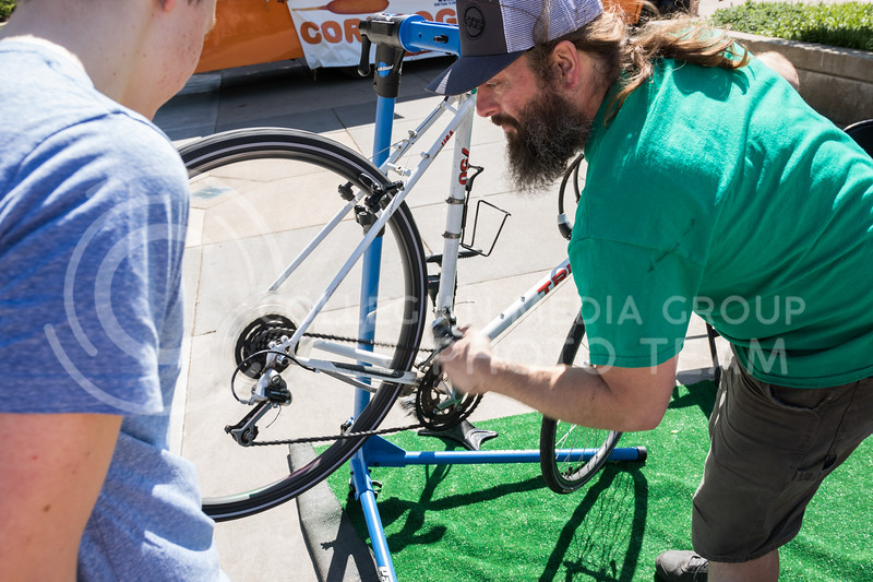 Sophomore in chemical engineering, Jack Gerhold has his bicycle tuned up for free by Brew Bros' Clint McAllister at the Green Apple Bikes Ride2Campus event in Bosco Plaza on Apr. 24, 2017. (John Benfer | The Collegian)