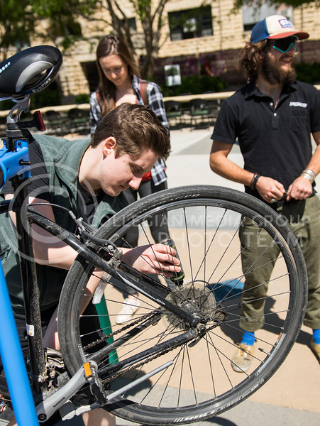 Pathfinder's Miranda Martin tunes up a bicycle at the Green Apple Bikes Ride2Campus event in Bosco Plaza on Apr. 24, 2017. (John Benfer | The Collegian)