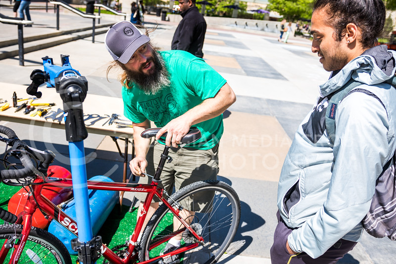 Brew Bros' Clint McAllister tunes up the bicycle of Yuvi Dodiya, sophomore in architecture, at the Green Apple Bikes Ride2Campus event in Bosco Plaza on Apr. 24, 2017. (John Benfer | The Collegian)