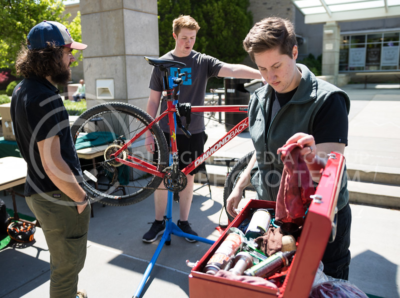 Pathfinder's Miranda Martin grabs a rag from the toolbox while tuning up a bicycle at the Green Apple Bikes Ride2Campus event in Bosco Plaza on Apr. 24, 2017. (John Benfer | The Collegian)