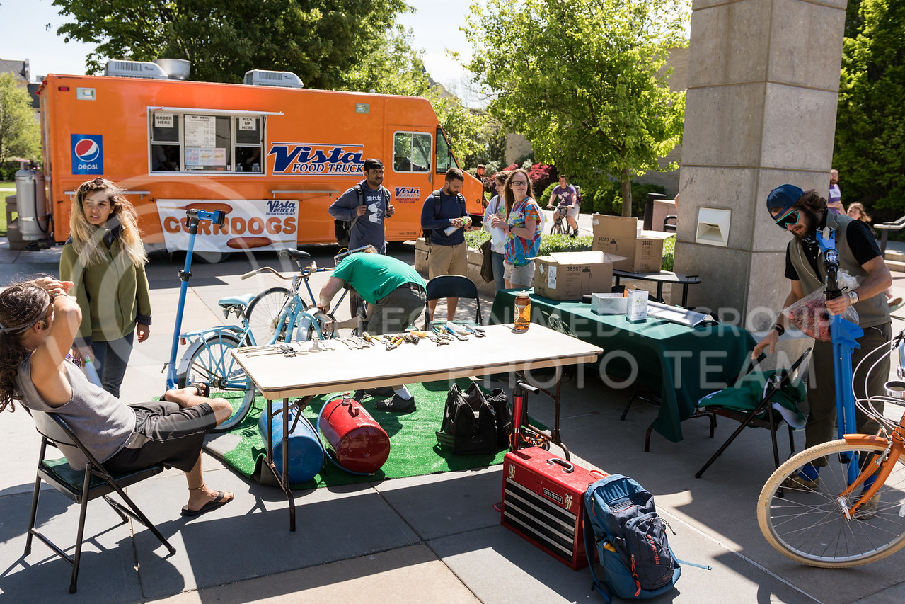 Students gather as Brew Bros' Clint McAllister tunes up a bicycle at the Green Apple Bikes Ride2Campus event in Bosco Plaza on Apr. 24, 2017. (John Benfer | The Collegian)