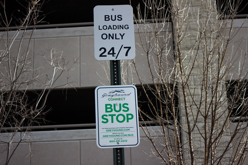 The bus stop sign posted next to the sidewalk in front of the K-State parking garage is one of the new additions since the Greyhound bus service has begun running. The Greyhound bus service runs once a day to Salina, KS and Kansas City, MO, with the Salina bus leaving at 11:55 am and the Kansas City bus leaving at 3:45 pm. (Sarah Millard | Collegian Media Group)