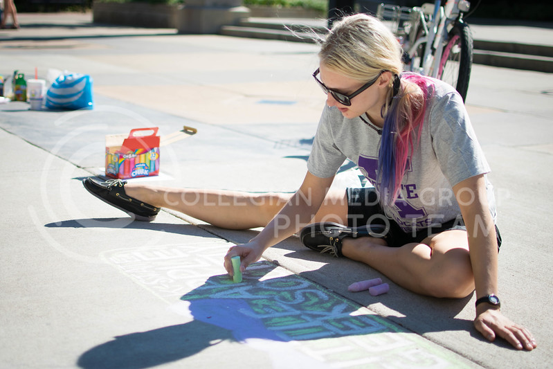 Chelsey Glatz, graduate in masters kinesiology, draw for the chalking competition Oct. 16.<br /> (Meg Shearer | The Collegian)