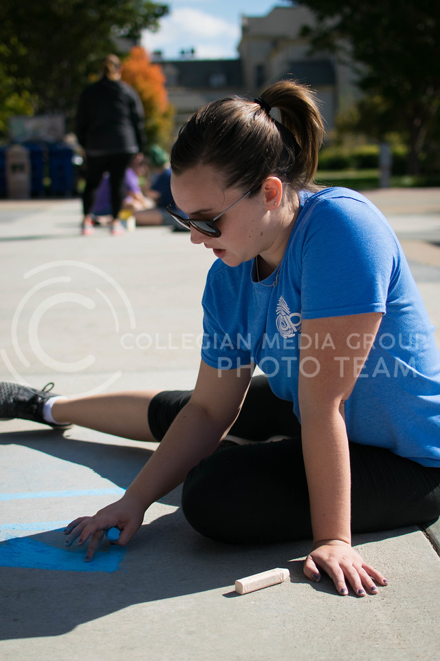 Rachael Herter, senior in English, spreads chalk for the Union Program Council chalk art on Oct. 16.<br /> (Meg Shearer | The Collegian)