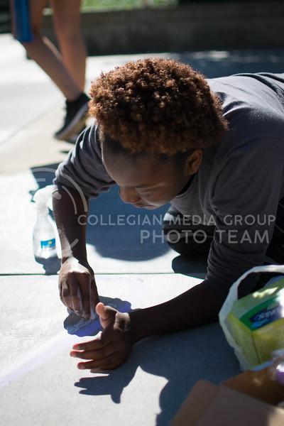 Krista Primers, sophomore in social work, draw for the Black Student Union's chalk art on Oct. 16.<br /> (Meg Shearer | The Collegian)