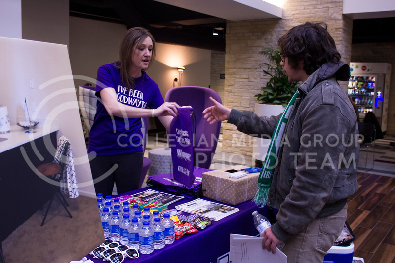 Isaiah Schmitt, senior at McPherson High School accepts a drawstring bag from the WoodWay Apartment table at the Housing Fair on Feb. 7, 2018 in the Union Courtyard. (Andrea Klepper   Collegian Media Group)
