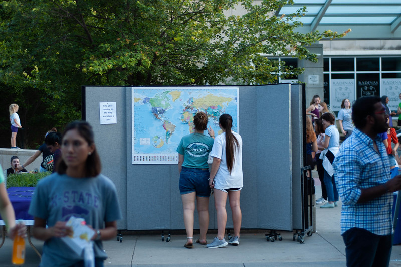 A map covered with pins from different home nations draws juniors Amelia Broadfoot and Briana Vaughns attention. The map was part of the activities set up by the K-State Alumni association for the 2018 International Block Party. (Rowan Jones | Collegian Media Group)