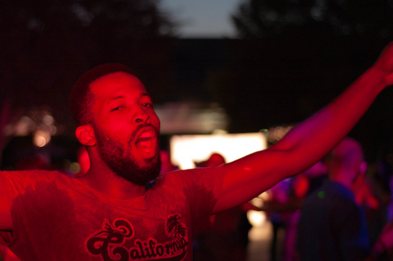 Drenched in sweat from dancing, an unknown man extends his arms and lets a cheer at the International Block Party in 2018. The party feature DJ Panama who played music from various International cultures. (Rowan Jones | Collegian Media Group)