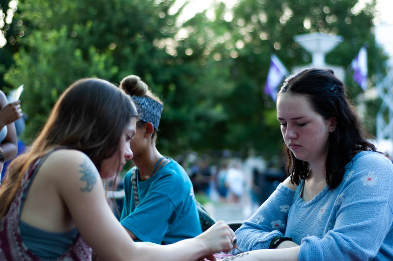 As her hand is painted by a Henna tatoo artist from Veronica's Veil, Freshman Ella Jung, watches. The Alumni Association provided free Henna tatoos at the International Block Party on Friday, August 24th, 2018. (Rowan Jones | Collegian Media Group)