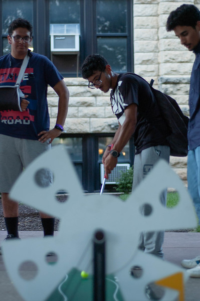 Standing over Freshman Hassan Bahakim, Freshmen Faisal Almutairi and Omar Abkar coach him on the mini golf course. All 3 aviation majors came to the International Block Party in Bosco Square, despite current enrollment at Salina, Polytechnic. (Rowan Jones | Collegian Media Group)