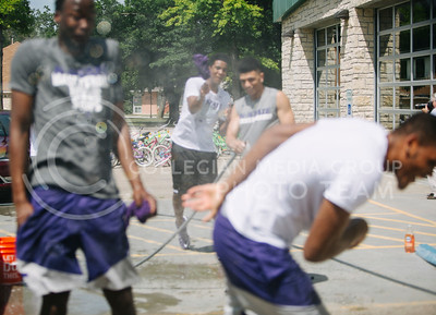 Mike McGuirl, men's basketball freshman guard, sprays his teammates during car competition during the Juneteenth celebration in City Park on June 6, 2017. (Emily Starkey | The Collegian)